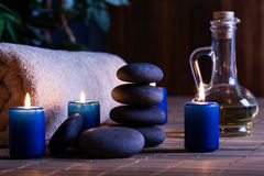 Spa still life with hot stones essential oil and candles Royalty Free Stock Photo
