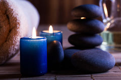 Spa still life with hot stones essential oil and candles Royalty Free Stock Images