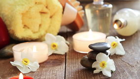 Spa still life of massage oil, towel, rocks and flowers stock video footage