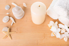 Spa still life with orchid, stones, candle burning and towel Royalty Free Stock Photography