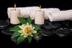 Spa still life of passiflora flower, green leaf with drop, towel. S and candles on zen stones in reflection water, closeup royalty free stock photo