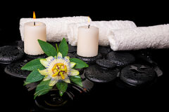 Spa still life of passiflora flower, green leaf with drop, towel. S and candles on zen stones in ripple reflection water, closeup royalty free stock photos