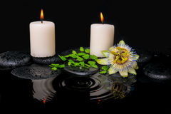 Spa still life of passiflora flower, green leaf fern with drop. And candles on zen stones in ripple reflection water, closeup stock photography