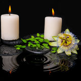 Spa still life of passiflora flower, green leaf fern with drop. And candles on zen stones in ripple reflection water, closeup stock images