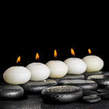 Spa still life of row white candles on black zen stones Stock Photography
