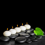 Spa still life of row white candles and green leaf on black zen Royalty Free Stock Photography