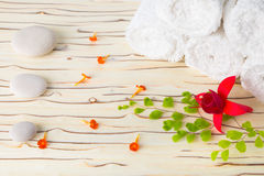 Spa still life with stone, flowers  and white towel on wood Royalty Free Stock Photo