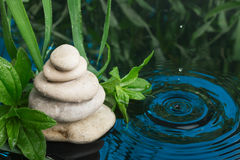 Spa still life with stone pyramid reflecting in water Royalty Free Stock Image
