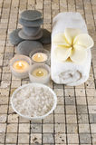 SPA still life. On stone tile: bath salt,candles, frangipani-shaped soap on towel and stack of stones Royalty Free Stock Image