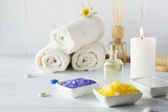 Spa still life with towel,white lily, sea salt, bath oil, sugar body scrub, massage brush. And candle royalty free stock photos