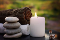 Spa still life with towels, a burning candle, bath oil and massage stones against the backdrop of a green garden.  stock images
