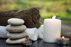 Spa still life with towels, a burning candle, bath oil and massage stones against the backdrop of a green garden in summer. Spa still life with towels, a burning stock photos