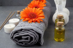 SPA still life with towels, oil, massage balls and gerbera flowers on a grey surface. SPA still life with towels, oil, massage balls and gerbera flowers on a royalty free stock photos