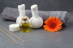 SPA still life with towels, oil, massage balls and gerbera flowers on a grey surface. SPA still life with towels, oil, massage balls and gerbera flowers on a stock images