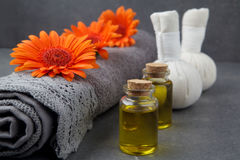 SPA still life with towels, oil, massage balls and gerbera flowers on a grey surface. SPA still life with towels, oil, massage balls and gerbera flowers on a stock photography