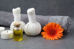 SPA still life with towels, oil, massage balls and gerbera flowers on a grey surface. SPA still life with towels, oil, massage balls and gerbera flowers on a stock photos
