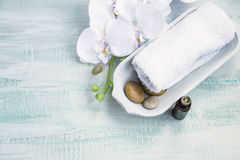 Spa still life. With white orchid and towel, bath essence oil bottle Stock Image
