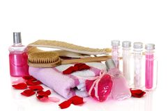 Spa still live. Spa essentials surrounded by rose petals on white background, reflective surface Royalty Free Stock Images