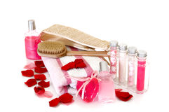 Spa still live. Spa essentials surrounded by rose petals on white background, reflective surface Royalty Free Stock Photos