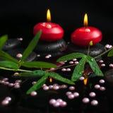 Spa stilleben av passiflorafilialen, pärlapärlor och röda stearinljus Royaltyfri Bild