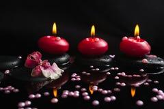 Spa stilleben av röda stearinljus, zenstenar med droppar, orkidé Royaltyfria Bilder