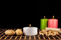 Spa stilleben med aromatiska stearinljus över svart bakgrund Royaltyfri Bild