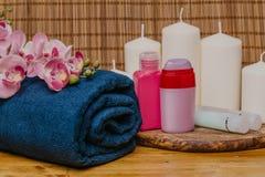 Spa stilleben med aromatiska stearinljus, orkidéblomman och handduken - Bild fotografering för bildbyråer