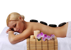 Spa Stone Massage. Blonde Woman. Spa Stone Massage. Beautiful Blonde Woman Getting Hot Stones Massage, isolated on white. Beauty Treatments Stock Photo