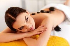 Spa Stone Massage. Young Woman Have Hot Stone Massage Treatments stock photo