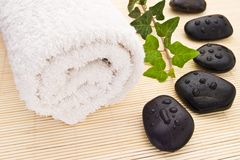 Spa stones. Towel ivy branch and spa stones with water-drops stock photography