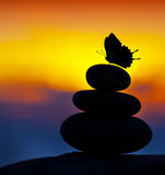 Spa stones balance. Colorful summer sky background, silhouette of stacked pebbles and butterfly, beautiful nature, peaceful beach sunset, conceptual image of
