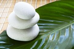 Spa stones on bamboo mat. White spa stones on leaf on bamboo mat Stock Photography