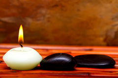 Spa stones and candles on bamboo Royalty Free Stock Image