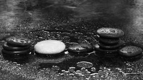 Spa stones on a dark background with water drops and reflection Royalty Free Stock Photo
