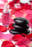 Spa stones, essential oil and rose petals Royalty Free Stock Photography