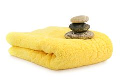 Spa stones on a folded yellow towel Royalty Free Stock Photo