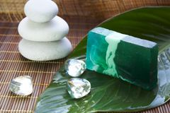 Spa stones, leaf and soap on bamboo mat. Spa stones, leaf and green soap on bamboo mat Royalty Free Stock Photo