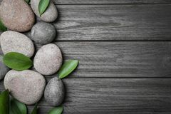 Spa stones and leaves. On wooden background Stock Photos