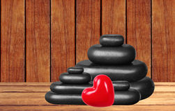 Spa stones and red heart on wooden table over wooden Royalty Free Stock Photo