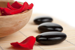 Spa stones and rose petals in bowl isolated Royalty Free Stock Photography