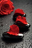 Spa stones and rose petals over black background Stock Photography