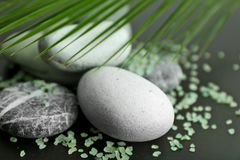 Spa stones and scattered sea salt on table, closeup royalty free stock photo