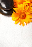 Spa stones on white towel with orange flower Stock Images