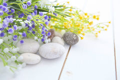Spa stones with wild flowers on wooden table Royalty Free Stock Photo