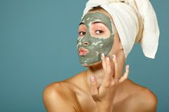 Spa teen girl applying facial clay mask. Beauty treatments. Over blue background Stock Photo