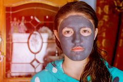Spa teen girl applying facial clay mask. Beauty treatments. Over blue background. Mask on the face of a young girl Royalty Free Stock Photography