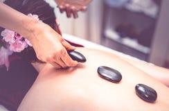 Spa terapeut som förlägger på den varma stenen till kvinnor tillbaka Arkivbild