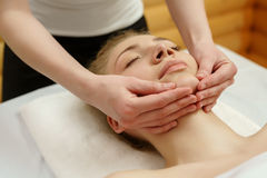 Spa Terapeuta del masaje que da masajes al client& x27; barbilla de s Imagen de archivo libre de regalías