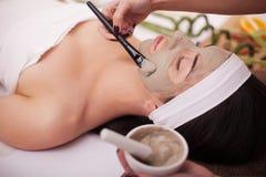 Spa terapi för den unga kvinnan som har den ansikts- maskeringen på skönhetsalongen - inomhus arkivfoto