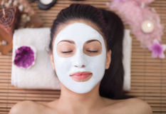 Spa terapi för den unga kvinnan som har den ansikts- maskeringen på skönhetsalongen Arkivbilder